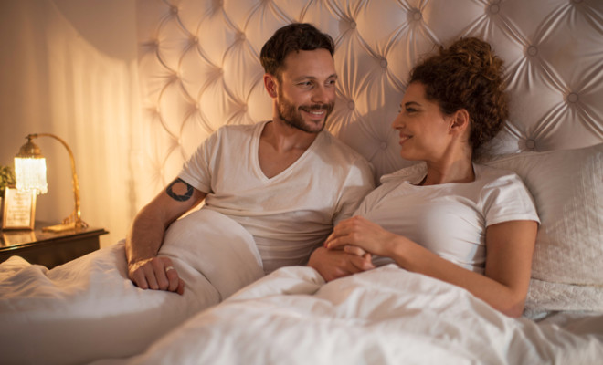 Young loving couple relaxing in bed and communicating.