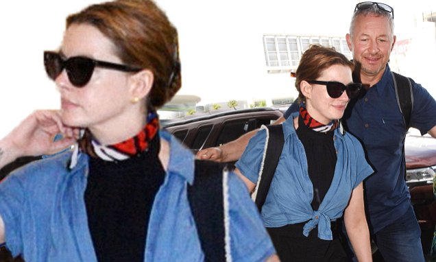EXCLUSIVE: Actress Anne Hathaway carrying dog in bag with her departing from LMM airport in  San Juan, Puerto Rico,